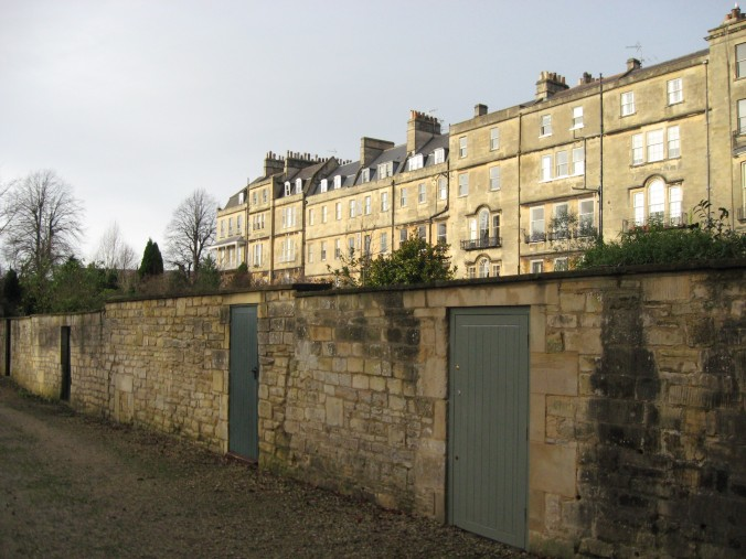 The backs of houses seen from a footpath near the Crescent. There's a public garden up the way.