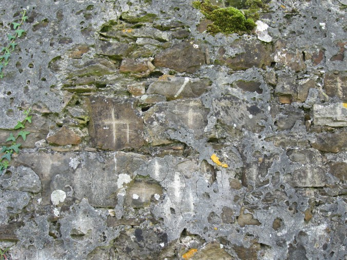 Crosses scratched by visitors in the wall near St Declan's Well.