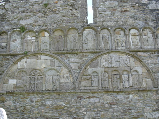 The carvings on the outer ruins of the church by the tower, featuring Biblical scenes.